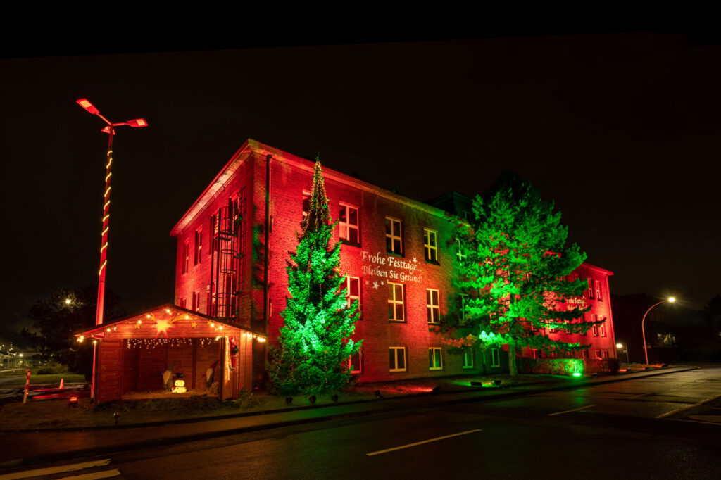 Das Gebäude der EVONIK mit einer weihnachtlichen Illumination von M4E Veranstaltungstechnik. Das Gebäude ist rot angestrahlt und die Bäume davor in grünes Licht getaucht.