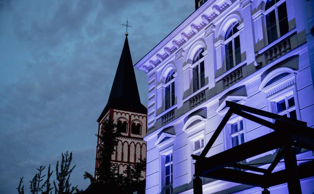 Violett illuminierte Gründerzeitfassade vor der Siegburger Kirche. Eine Installation von M4E Veranstaltungstechnik.